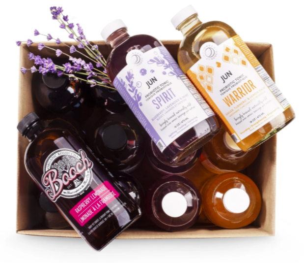 set of many glass bottles filled with various kinds of kombucha with three exposed to show flavours some sitting on pieces of lavendar
