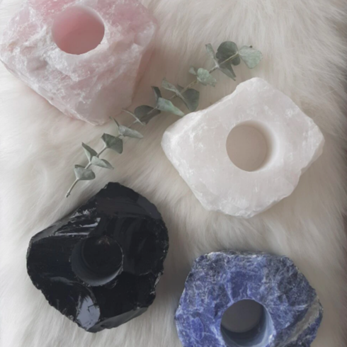 set of four different coloured candle holders sitting on a fur fabric with euchalyptus leaves in view