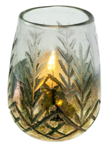 small candle holder with engraved pine needle shapes at the bottom with lit flame inside