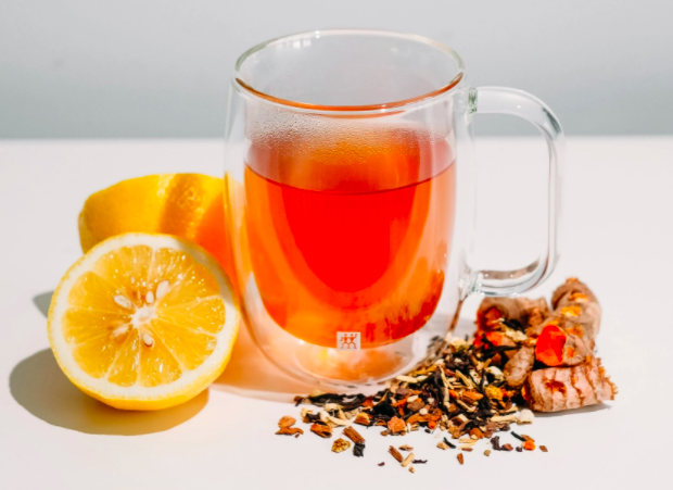 small glass teacup with orange loose leaf tea inside with leaves laid out in front of cup with a cut open lemon against a white background