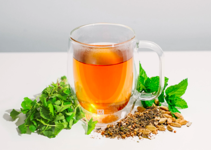 small glass teacup with orange loose leaf tea inside with leaves laid out in front of cup with a bushel of mint against a white background