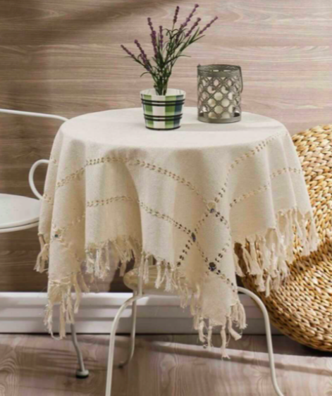 small dining room table with beige table cloth on top that is tasseled with a plant and candle holder sitting on top