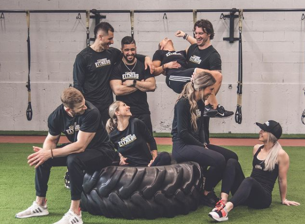 group of fitness instructors sitting and standing around a large tire smiling and laughing