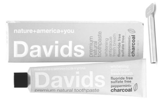 small white twist bottle of toothpaste with product details printed on the front and box sitting beside bottle