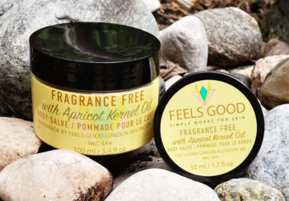 two different sized bottles of fragrance free body salve with yellow labelling on the front sitting amongst rocks outside