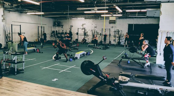Interior of a gym facility with various pieces of workout equipment and people working out all around the room with astro turf for flooring