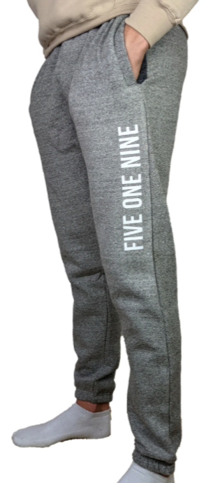 man modelling a pair of grey sweatpants that say five one nine going up the left leg where you can only see waist down