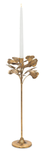 very tall golden candle holder with leaves coming out from the side with a tall white candle inside