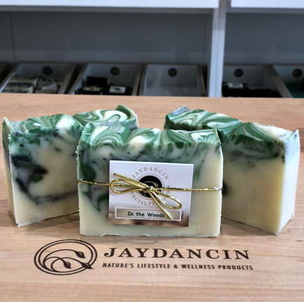 set of three handmade soap bars with green colouring throughout sitting on a wooden board
