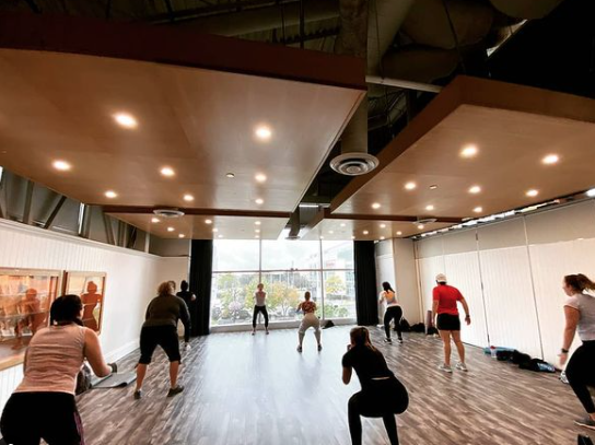 workout class with people spread out and squatting facing a large window