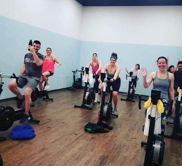group of people working out on bikes smiling at the camera with some waving
