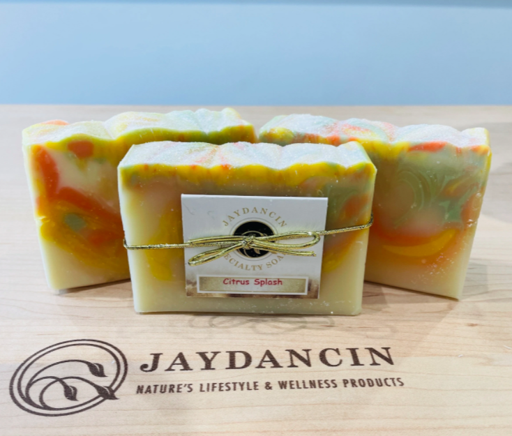 set of three handmade soaps in orange with twists of green wrapped with ribbon with a small branded card attached to the front sitting on a wooden cutting board