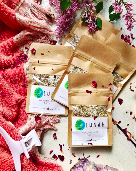 various brown paper packages of bath salts with different product labels on each sitting on a red towel amongst a hair clip and flower petals