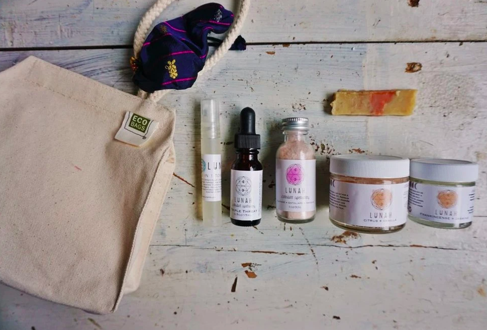 gift set of various skincare products in different sized vials and bottles with a bamboo carrying bag sitting on distressed white wood