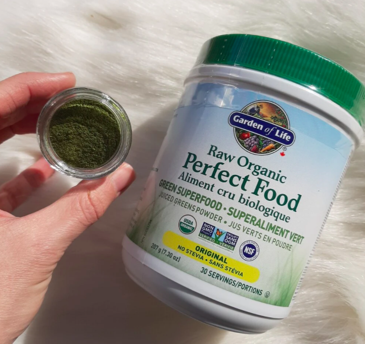 mid sized bottle of superfood powder with hand holding a small glass container of powder sitting above a fur carpet