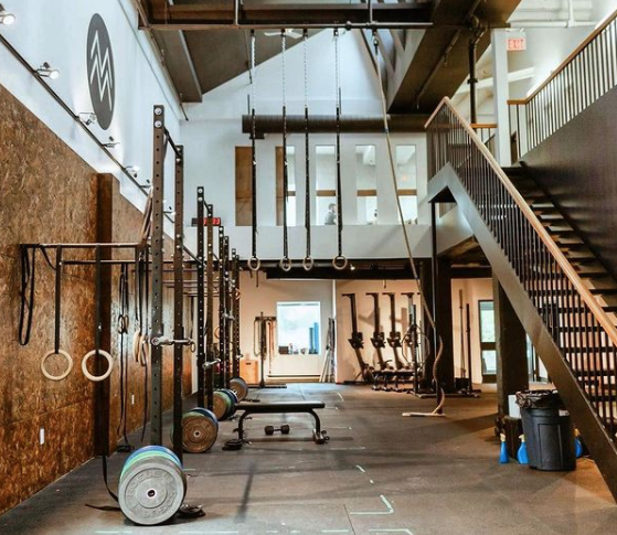Interior of a gym facility with various pieces of workout equipment with stairs going up to the right hand side