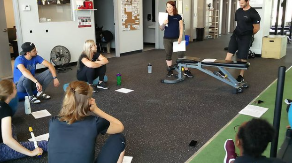 people sitting in a gym facility with various pieces of equipment around the room looking to instructor with piece of paper