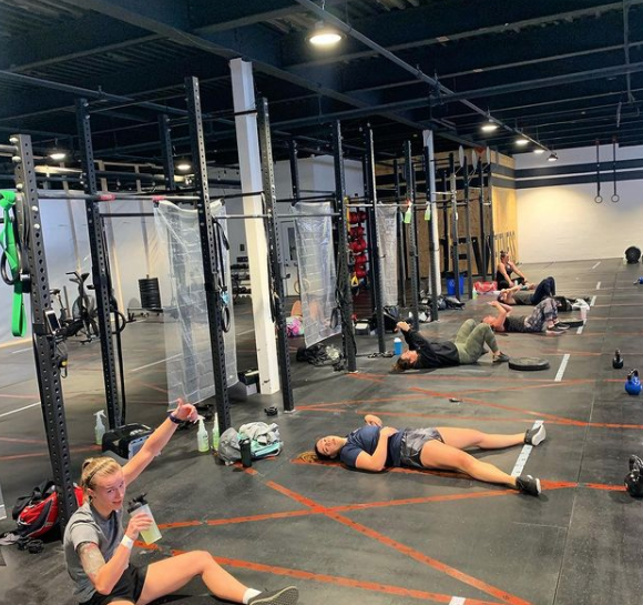 Interior of a gym facility with various pieces of workout equipment and people laying on the ground some drinking water