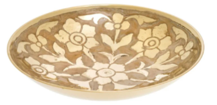 mid sized golden dish with flower type shapes engraved throughout against a white background
