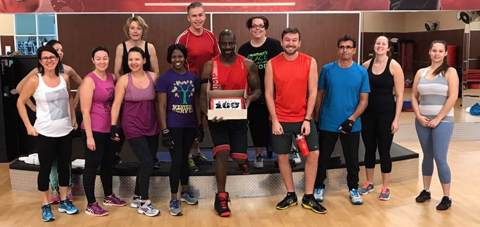 workout class posing for a photo with main instructor holding a cake