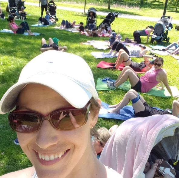 woman taking a selfie with other women laying on yoga matts with strollers beside in the backround
