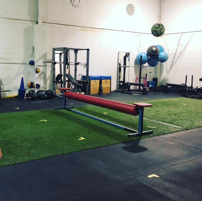 Interior of a gym facility with various pieces of workout equipment with astro turf on the ground