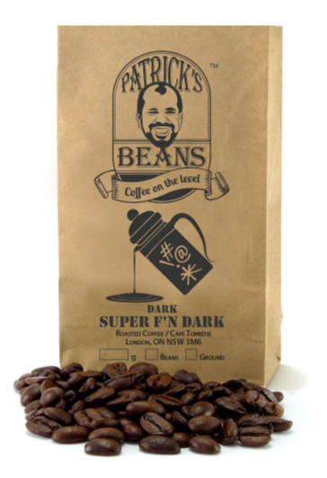 mid sized bag of full coffee beans with some beans laid out in front of paper bag against a white background