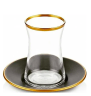 small glass unique shaped tea cup with golden rim sitting on a black saucer which also has a gold rim
