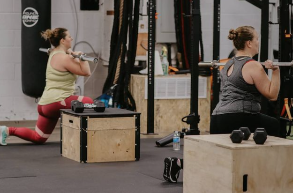 two women squatting with workout bars in their hands