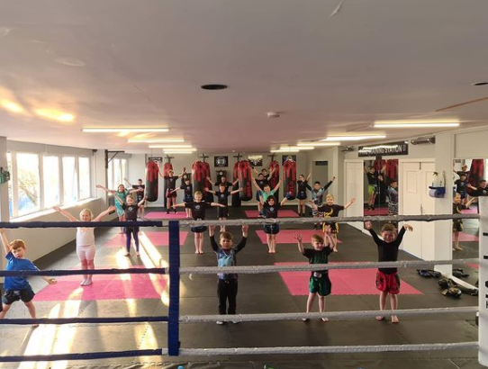 childrens workout class being taken from behind the ring with children with arms up in the backround