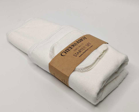small set of white cloth facial rounds wrapped in paper packaging against a white background
