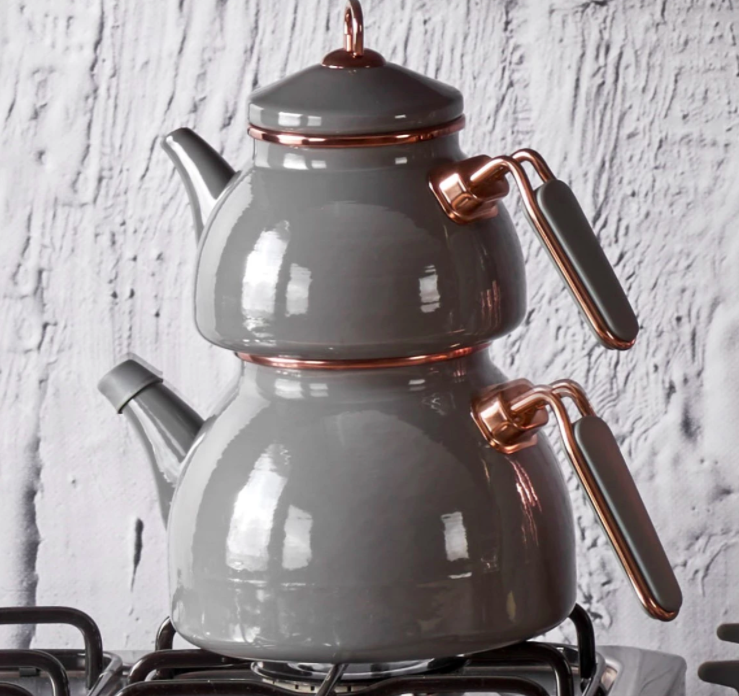 large grey double tea pot with rose gold detailing sitting on a stove
