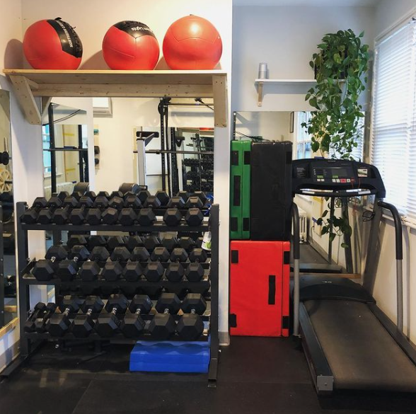 Interior of a gym facility with various pieces of workout equipment in a tight corner