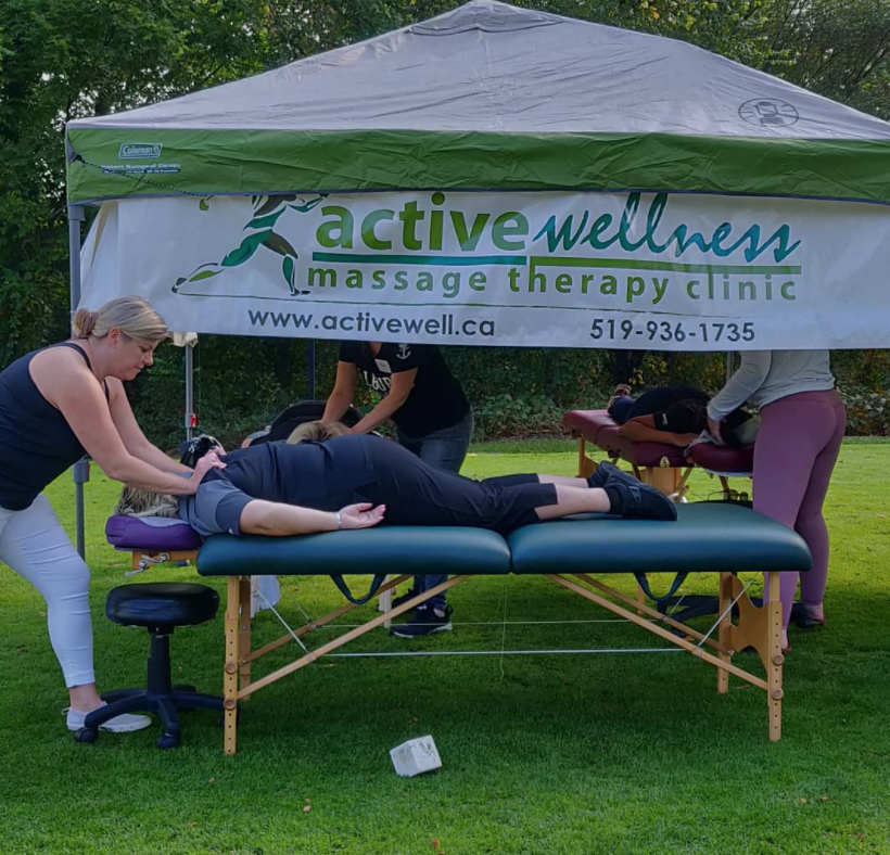 Woman performing a massage outdoors with a woman laying on a massage table face down under a branded tent