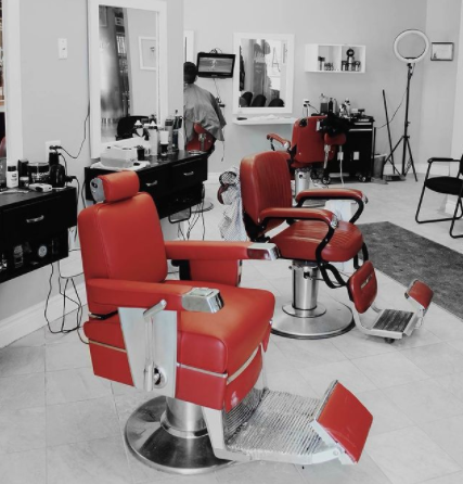 Interior of a barbershop with red accents and the rest of the photo in black and white