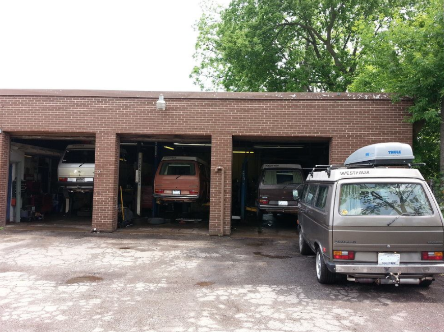 exterior of auto mechanic with three open garage doors with vans in each well and one van parked out front to the right