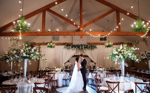 Interior of a wedding venue with bride and groom kissing in the middle room