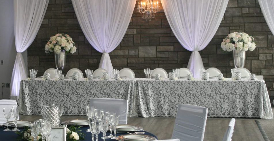 interior of a wedding venue looking at a set head table with light decor throughout