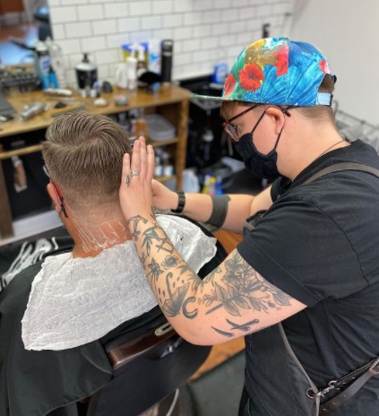 Picture of a haircut from a barber in a studio with stylist giving a shave