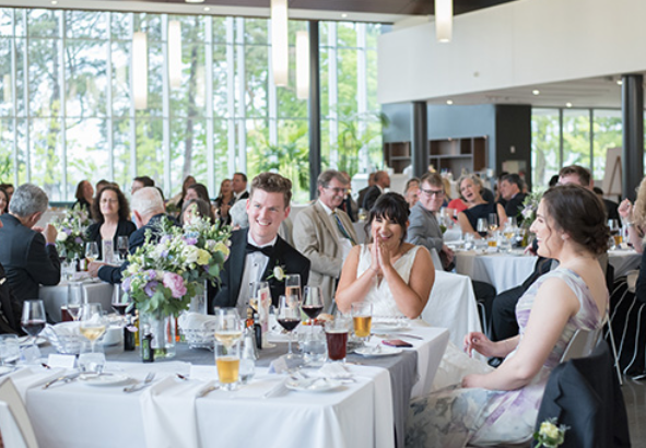 interior of a wedding venue with set tables and focus on the bride and groom smiling with all their guests