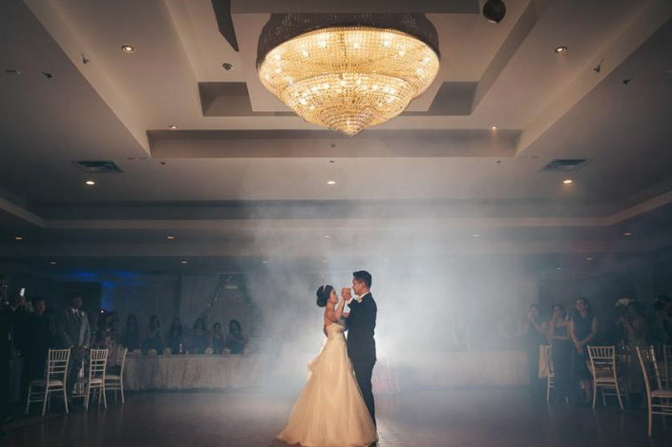 interior of a wedding venue with bride and groom doing first dance on a foggy dancefloor with guests gathered around