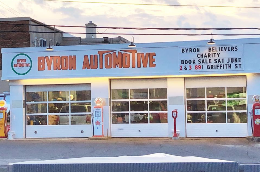 exterior of an auto mechanic with three closed garage doors at dusk with lights on the building