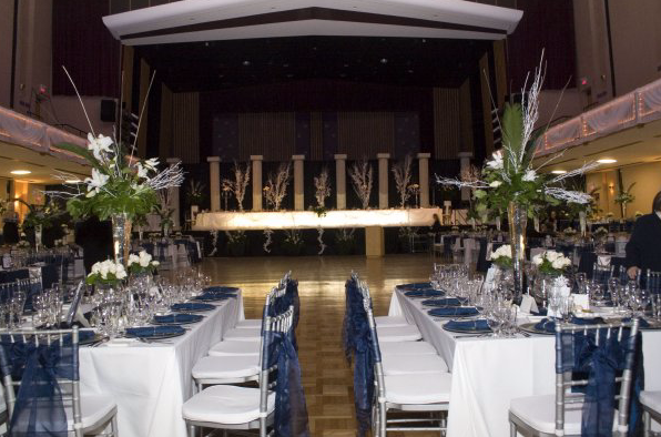 interior of a wedding facility with view of dance floor and set dinner tables with white and blue decor