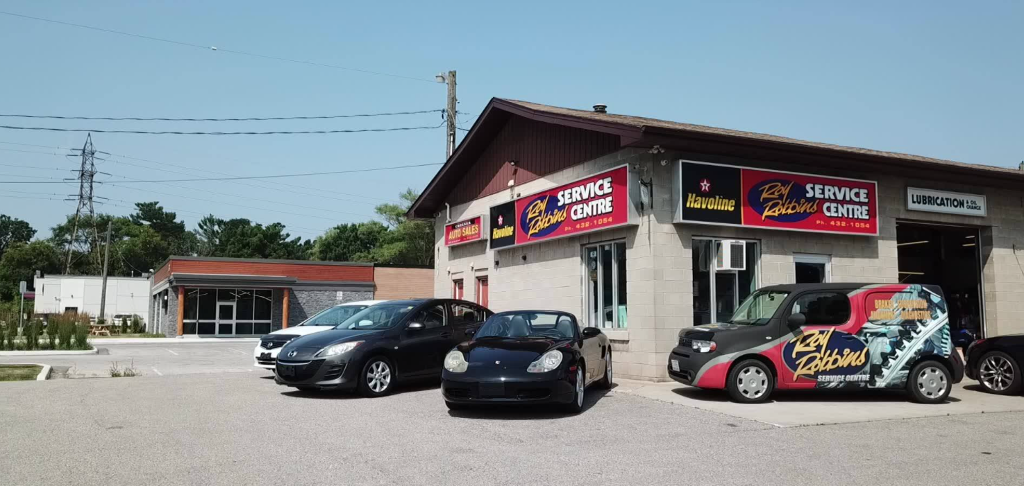 exterior of auto mechanic with a few different cars parked out front on a sunny day