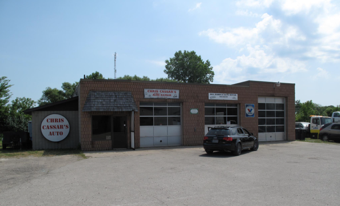 exterior of an auto mechanic with three closed garage doors with one audi parked out front