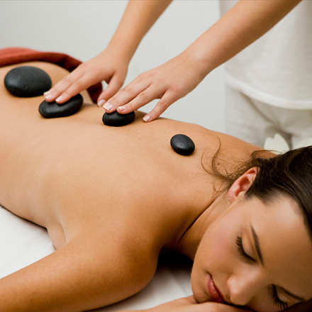 woman getting a hot stone massage laying down with various sized rocks on her back