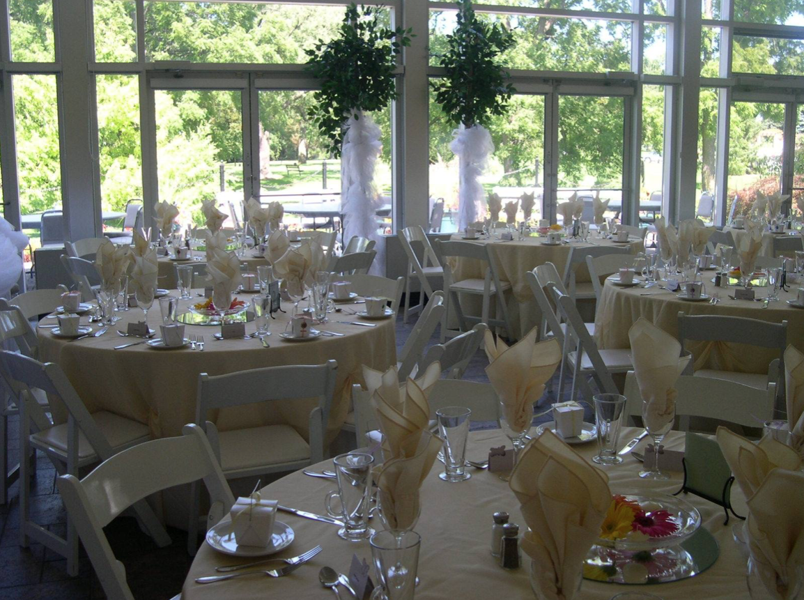 interior of a wedding venue with set tables looking out towards a garden