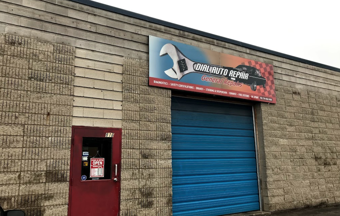 exterior of an auto mechanic with a closed blue garage door with an entry door to the left