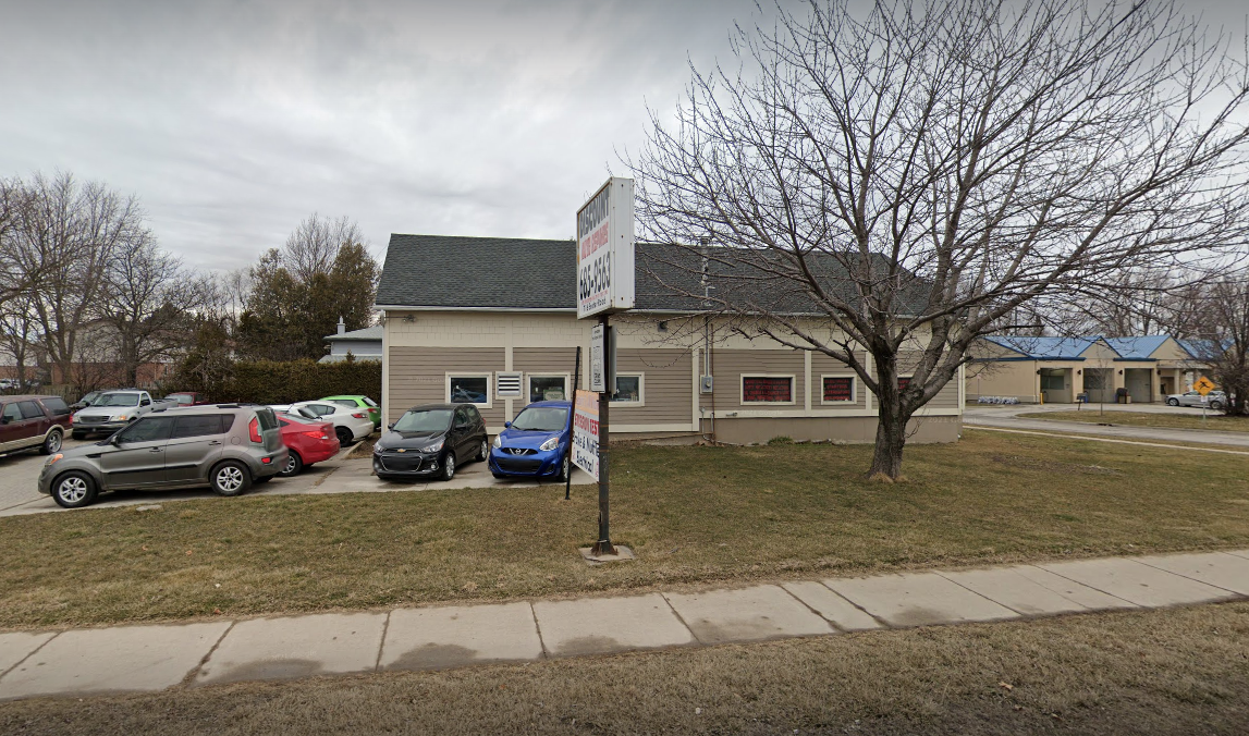 exterior of an auto mechanic with many cars parked out front on an overcast day