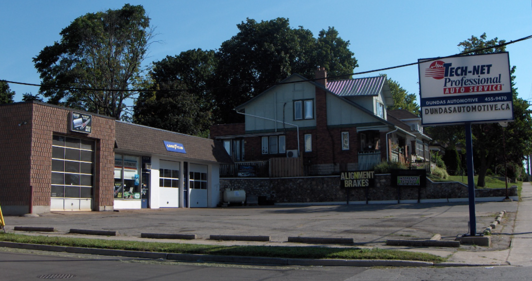 exterior of an auto mechanic with two closed garage doors beside an empty parking lot on a sunny day